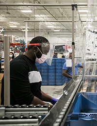 A man working on an assembly line wearing a mask, face shield and gloves
