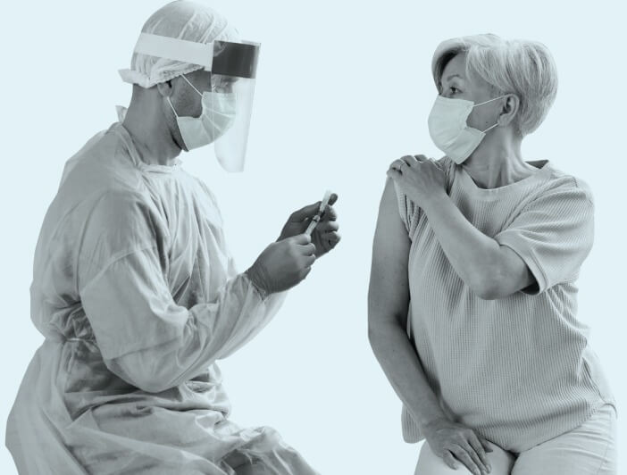 A person getting a vaccine shot from a healthcare worker with both wearing surgical masks