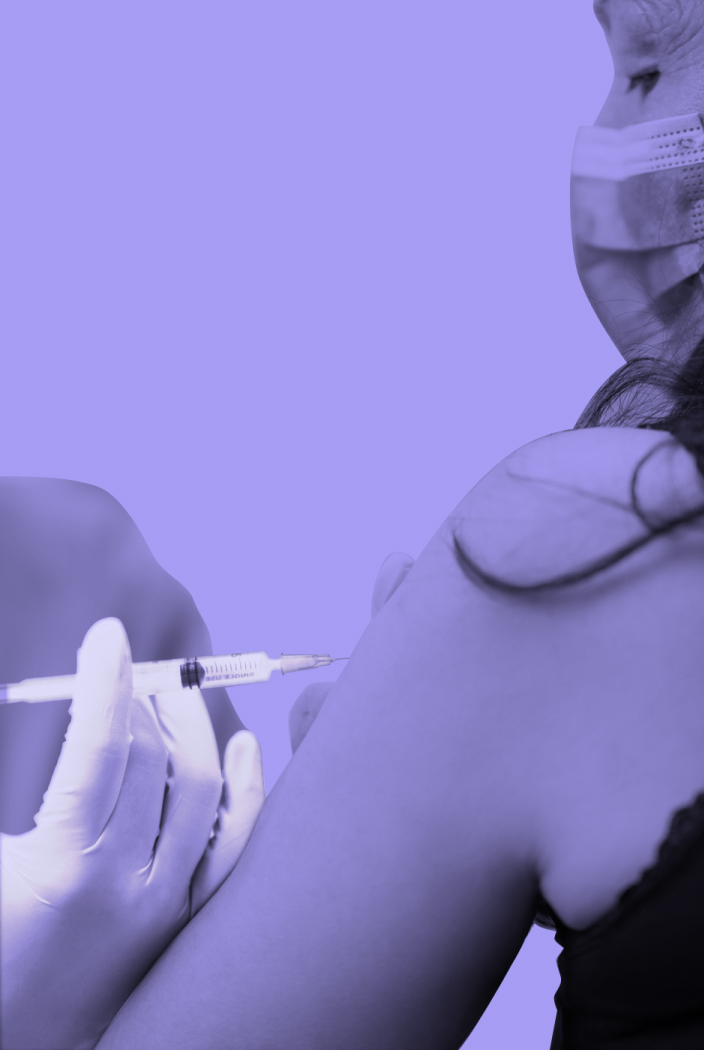 A person wearing a surgical mask receives a vaccine shot in their arm